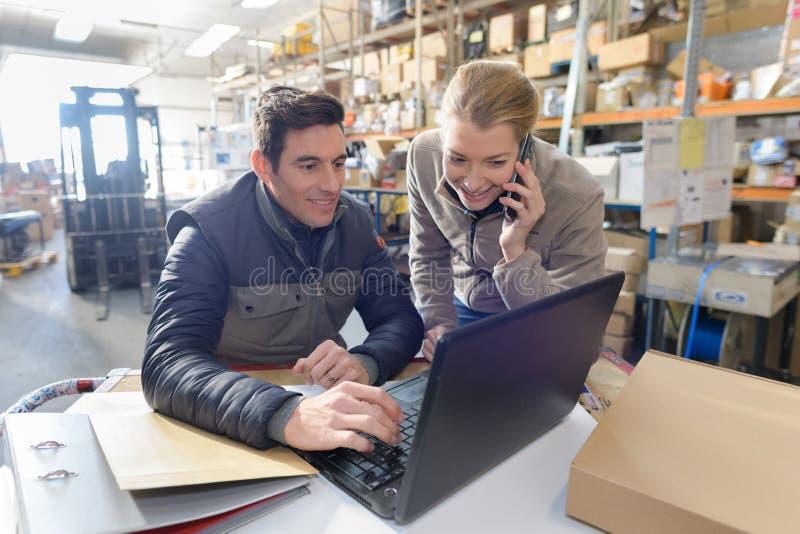 Responsabili che lavorano al computer portatile e che parlano sul telefono in magazzino fotografie stock libere da diritti