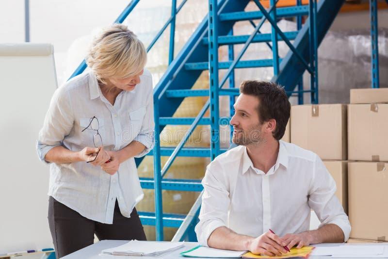 Responsabili del magazzino che parlano nel corso di una riunione immagine stock