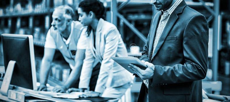 Responsabili e lavoratore del magazzino che lavorano insieme immagine stock