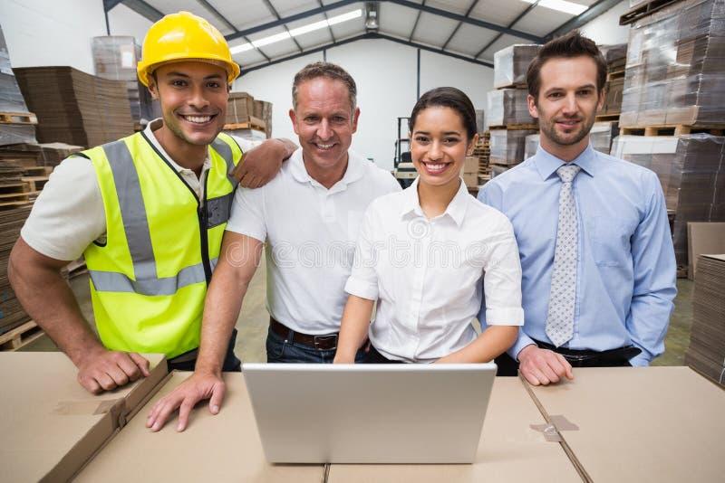 Responsabili e lavoratore del magazzino che sorridono alla macchina fotografica immagine stock