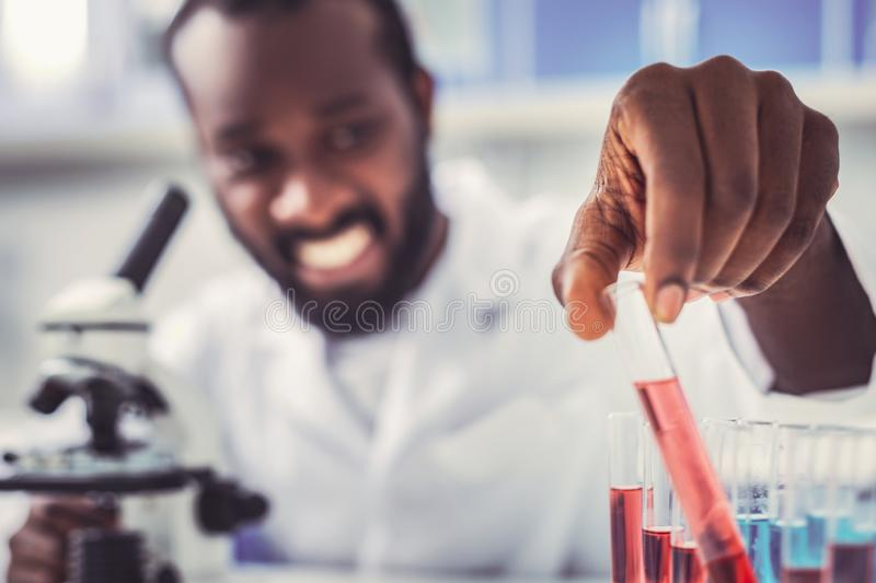 Responsible chemical assistant putting test tubes. Responsible assistant. Responsible chemical assistant feeling occupied while putting test tubes with colorful stock photo