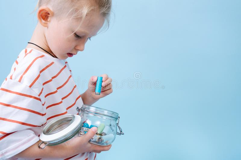 Responsible child is putting used batteries in a jar for recycling. royalty free stock image