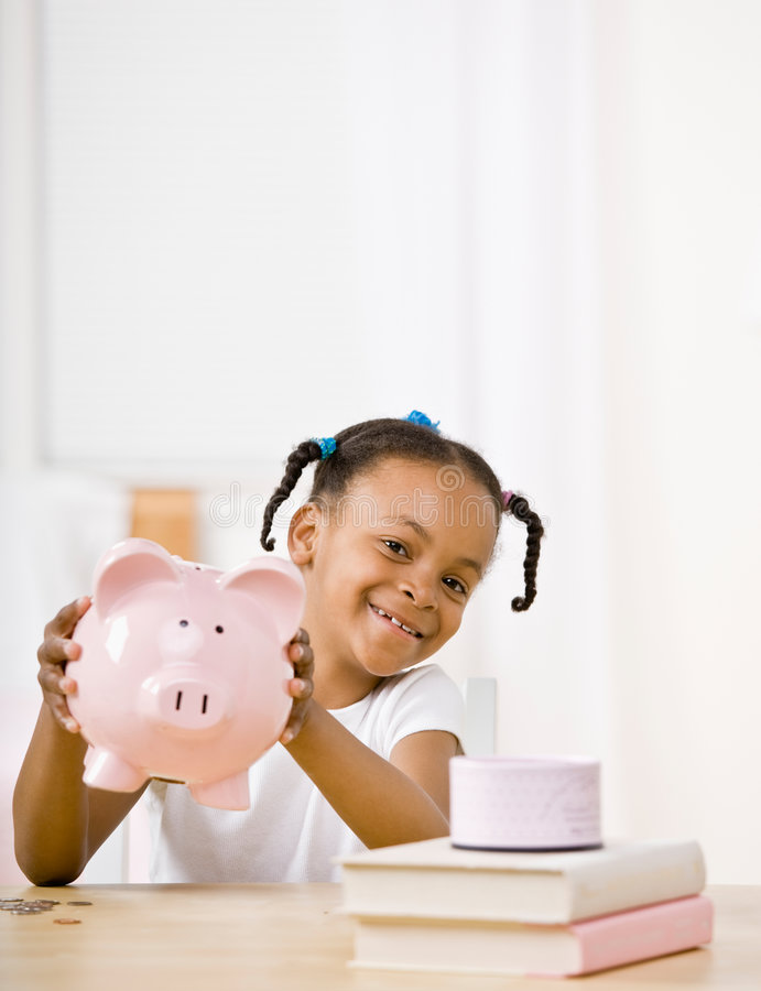 Responsible girl putting money into piggy bank. For future savings royalty free stock photography