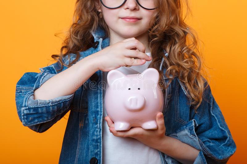 Financial concept of children`s pocket money. A child girl with piggy Bank on a colored orange background royalty free stock images