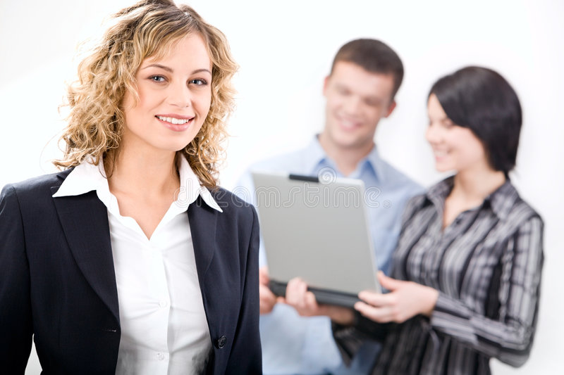 Responsible partner. Portrait of responsible partner with friendly smile on the background of business team royalty free stock image