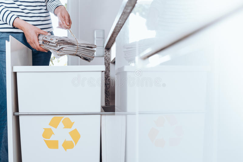 Responsible person sorting paper. Responsible person sorting waste in modern kitchen with special bin with yellow symbol for paper stock photo