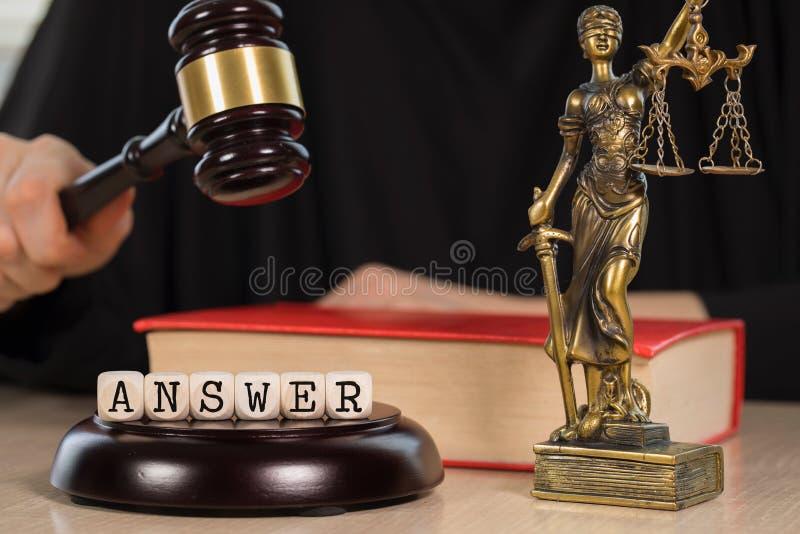A RESPOSTA da palavra composta de madeira corta Martelo e estátua de madeira de Themis no fundo fotografia de stock royalty free