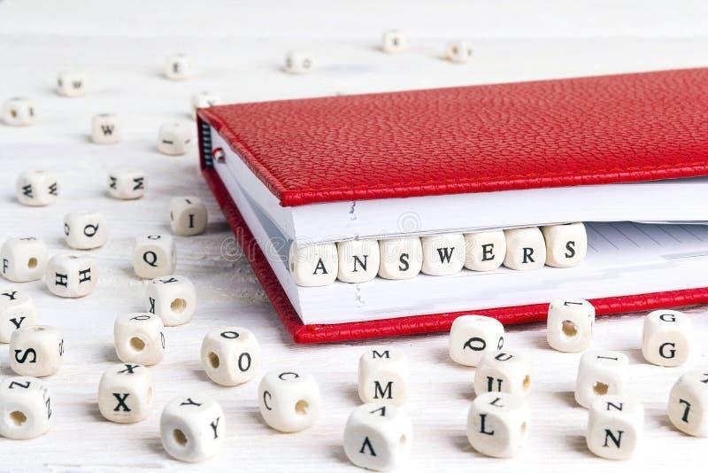 Respostas da palavra escritas em blocos de madeira no caderno vermelho em w branco imagem de stock