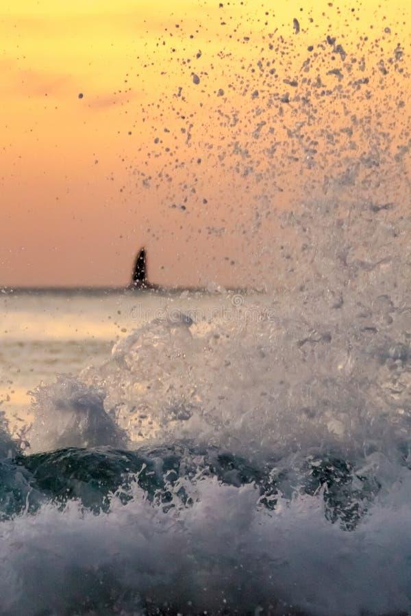 Ressac sur le coucher du soleil avec le bateau à l'horizon photographie stock