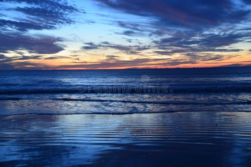 A ressaca do oceano brilha com cores primordiais enquanto a queda da noite começa fotografia de stock