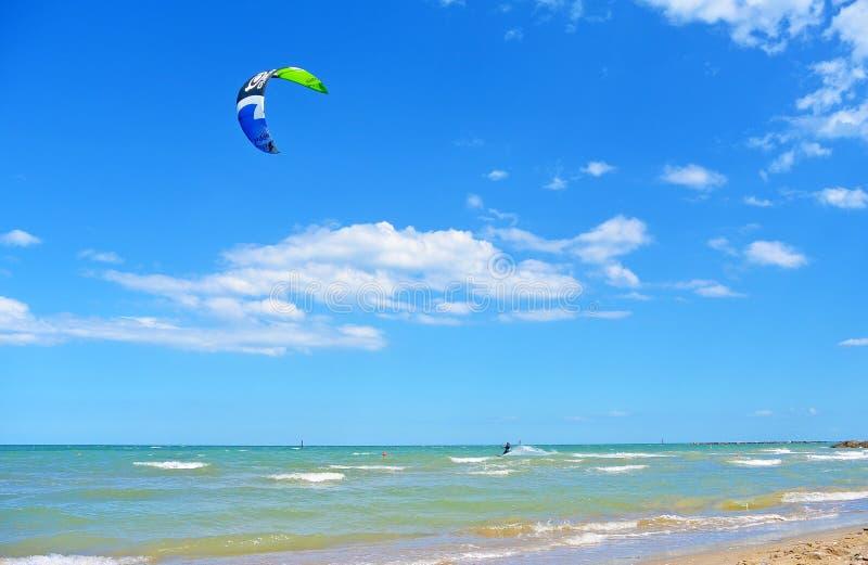 Ressaca do papagaio do passeio do homem novo no mar, no esporte extremo Kitesurfing ou kiteboarding imagem de stock