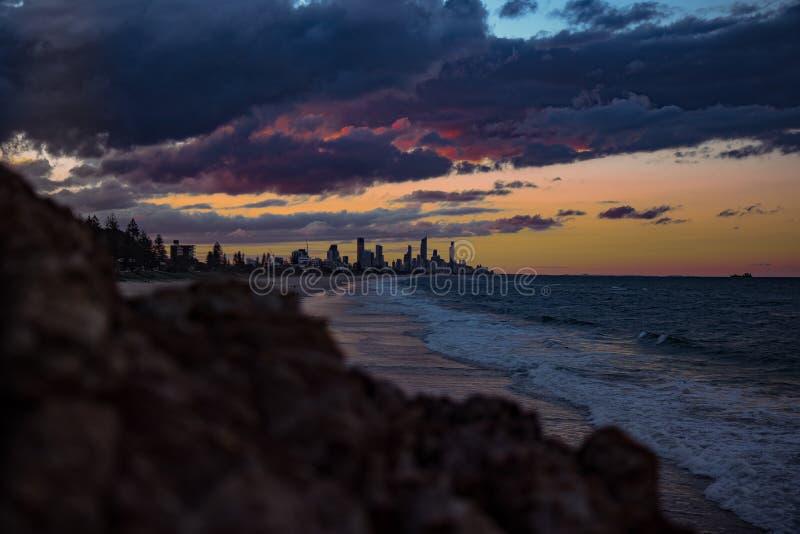 Ressacs et paysage urbain dans le coucher du soleil image stock