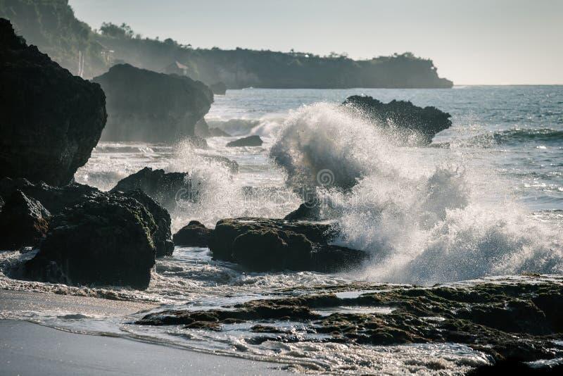 Ressacs se brisant sur les roches dans le coucher du soleil photographie stock