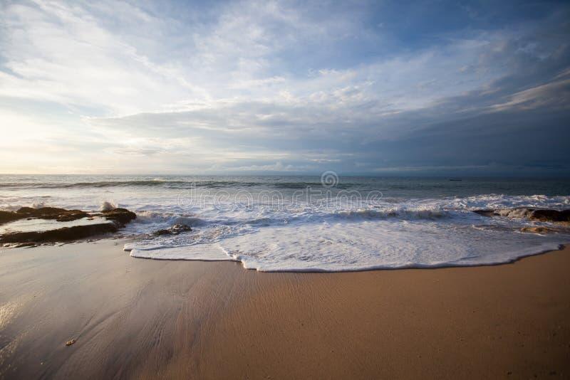 Ressacs se cassant sur les roches sur la plage photo stock