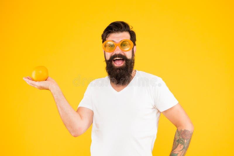 Ressemblez à un fruit toute votre vie Homme barbu tenant le fruit orange sur le fond jaune Hippie avec le casse-croûte sain de fr photo libre de droits