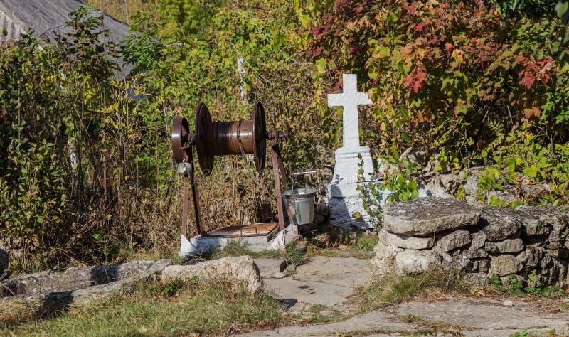 Ressort saint de l'eau vivante, murs couverts de mousse, automne Le puits d'eau saint avec une croix a bien alimenté l'eau de sou images stock