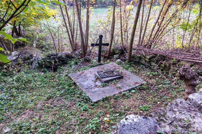 Ressort saint de l'eau vivante, murs couverts de mousse, automne Le puits d'eau saint avec une croix a bien alimenté l'eau de sou image libre de droits