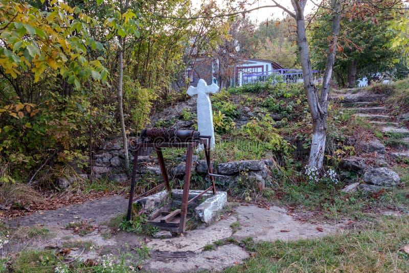 Ressort saint de l'eau vivante, murs couverts de mousse, automne Le puits d'eau saint avec une croix a bien alimenté l'eau de sou photographie stock