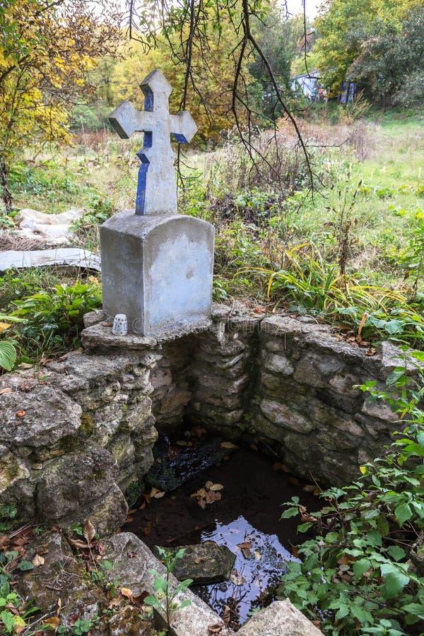 Ressort saint de l'eau vivante, murs couverts de mousse, automne Le puits d'eau saint avec une croix a bien alimenté l'eau de sou images libres de droits