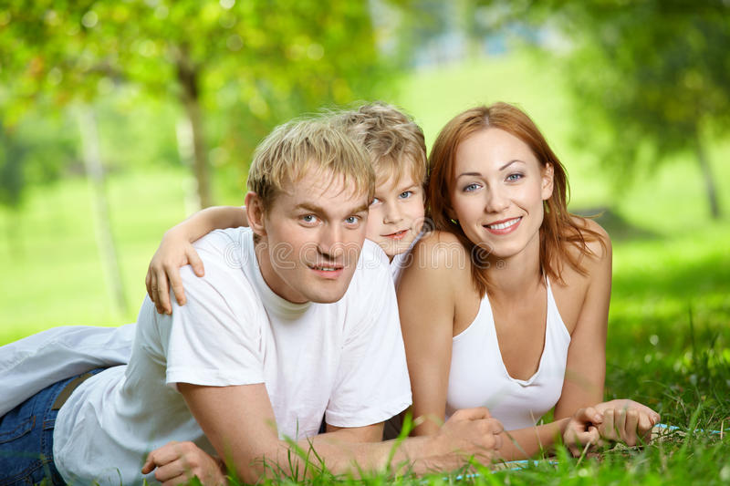 Rest. Young family consisting of three persons lies on a summer lawn royalty free stock photos