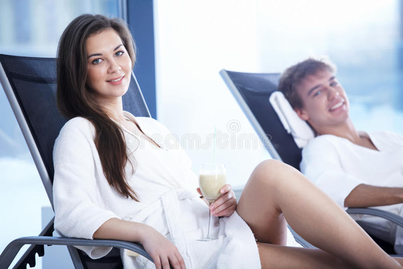 The rest. The girl and the guy have a rest on plank beds in an improving complex stock image