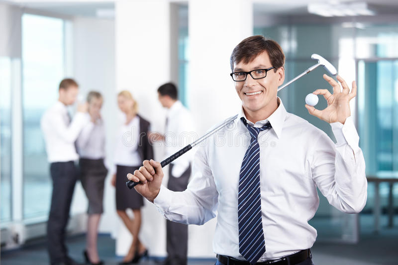 Rest. Businessman with a golf club against the staff office royalty free stock photo