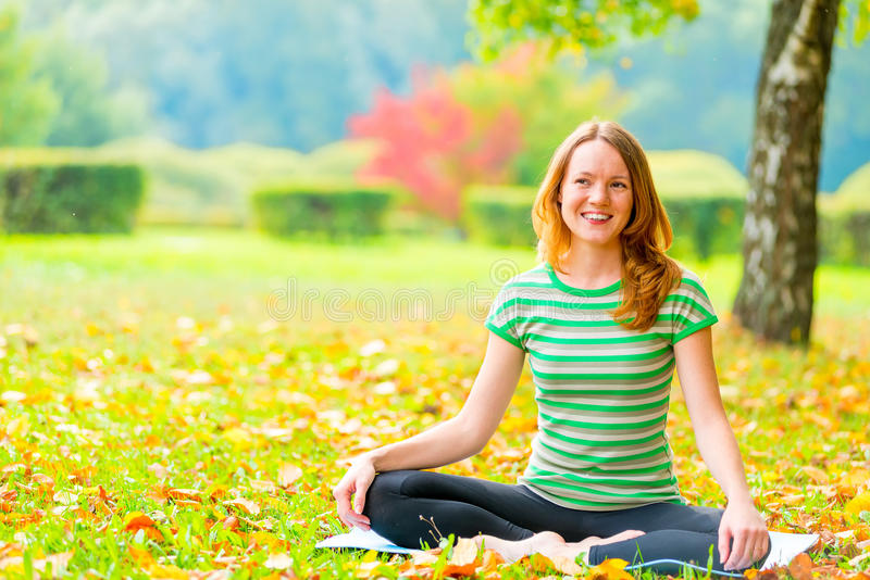 Rest in the autumn park. Woman practices yoga on the nature stock image