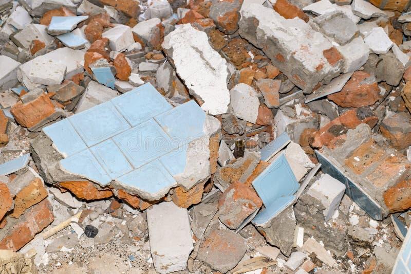 Rest av den förstörda väggen i form av stenar, tegelstenar, tegelplattor Bakgrund arkivbilder