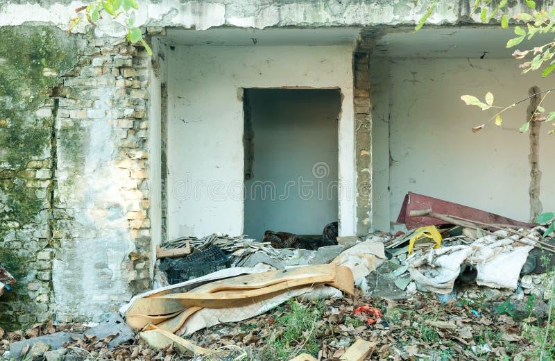 Rest av det demolerade huset samlade på högen som förstördes av granaten i staden under kriget royaltyfria bilder