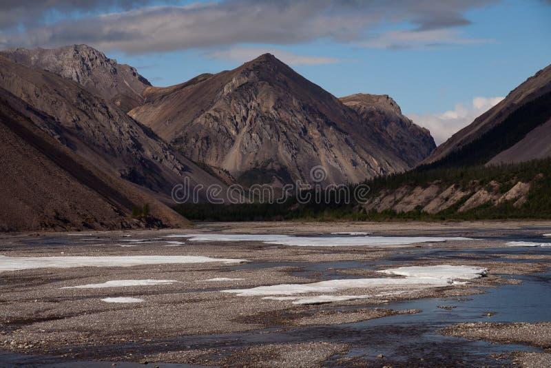 Rest av is i dalen av en bergflod fotografering för bildbyråer