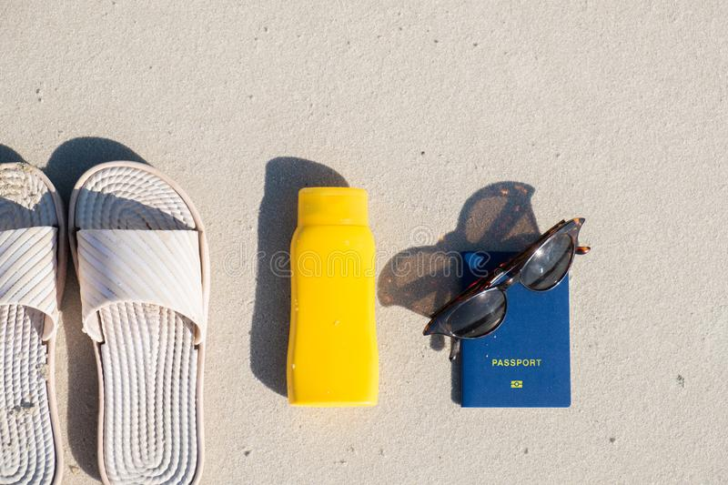 Rest on the beach: slippers, protective cream and sunglasses on clean sand. stock photography