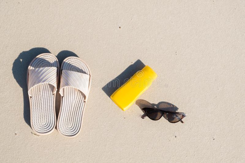 Rest on the beach: slippers, protective cream and sunglasses on clean sand. royalty free stock images