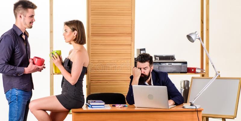 Rest break at work. Business partners enjoying conversation in lunch break while colleague working in background. Young stock image