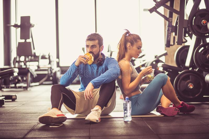 Rest and healthy food. Young couple at gym eating healthy food after exercise stock image