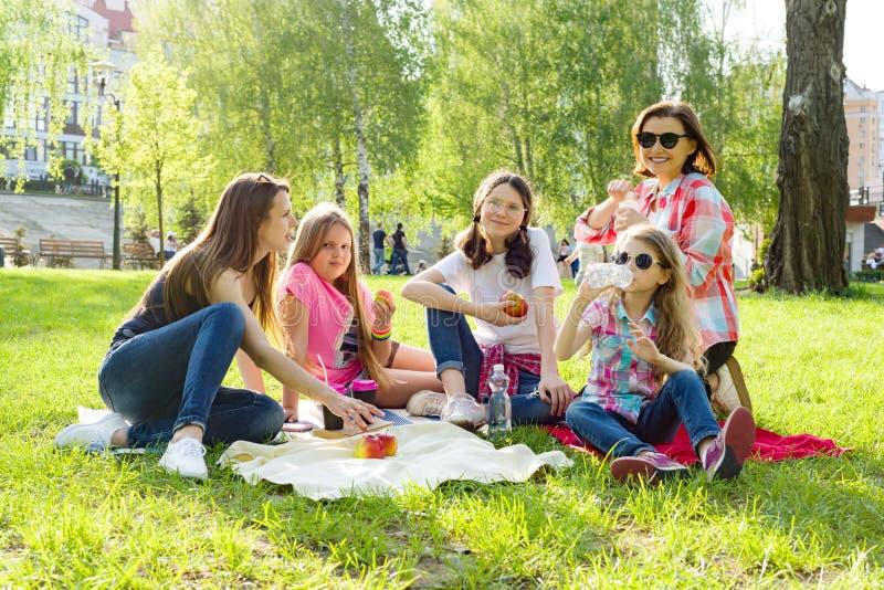 Rest im Park Mütter mit Kindern sitzen auf dem Gras, Frauengetränkkaffee, Kinder essen Äpfel stockfotografie