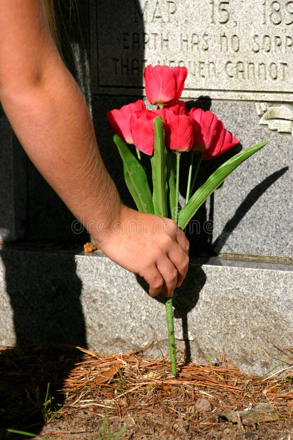Rest in peace. Hand placing flowers at a headstone royalty free stock image