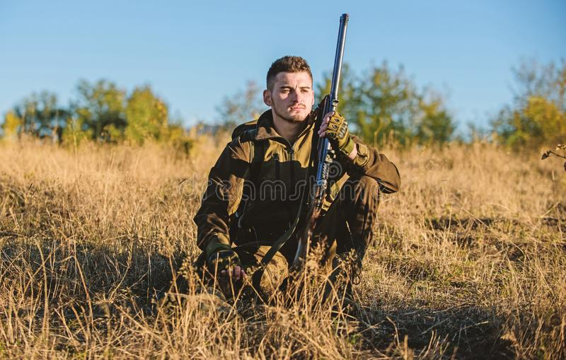Rest for real man concept. Hunter with rifle relaxing in nature environment. Tired but satisfied. End of season. Hunter stock photo