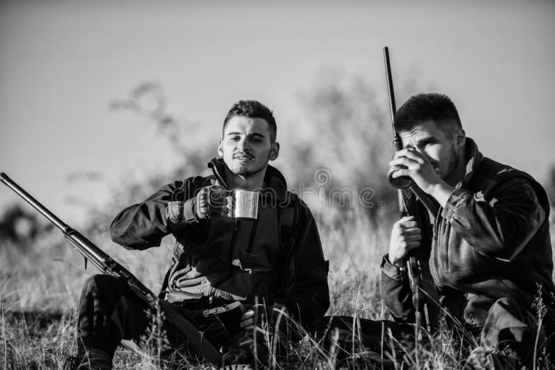 Rest for real men concept. Hunters with rifles relaxing in nature environment. Hunters friends enjoy leisure. Hunting royalty free stock photography