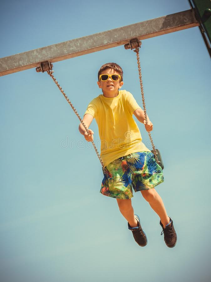 Boy playing swinging by swing-set royalty free stock photography
