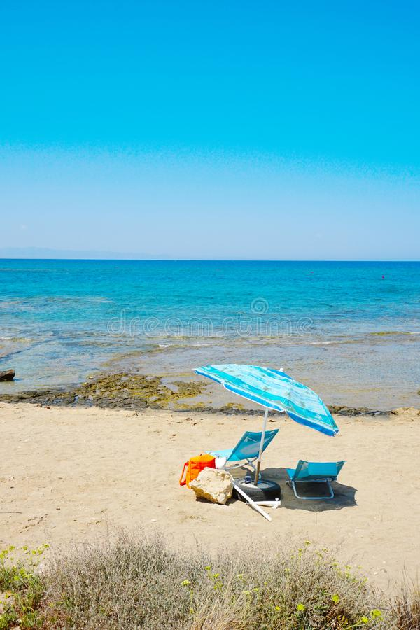 Umbrella and lounge chair are on the sea shore stock photography