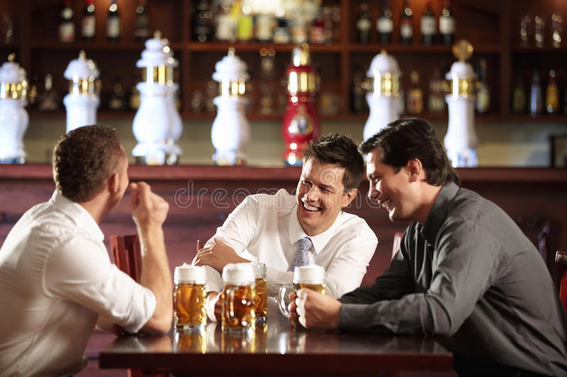 Rest after work. Three men in shirts in the bar royalty free stock photography