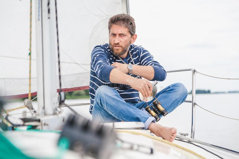 Man sits on bow of sailing yacht and holds jar royalty free stock photo