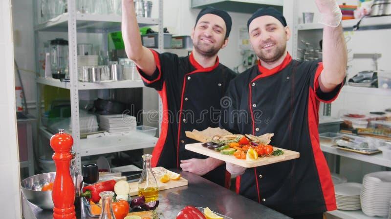 Restauracyjna kuchnia Dwa m??czyzna porcji szef kuchni ko?cz?cego naczynia z bellissimo gestykuluj? zdjęcie royalty free