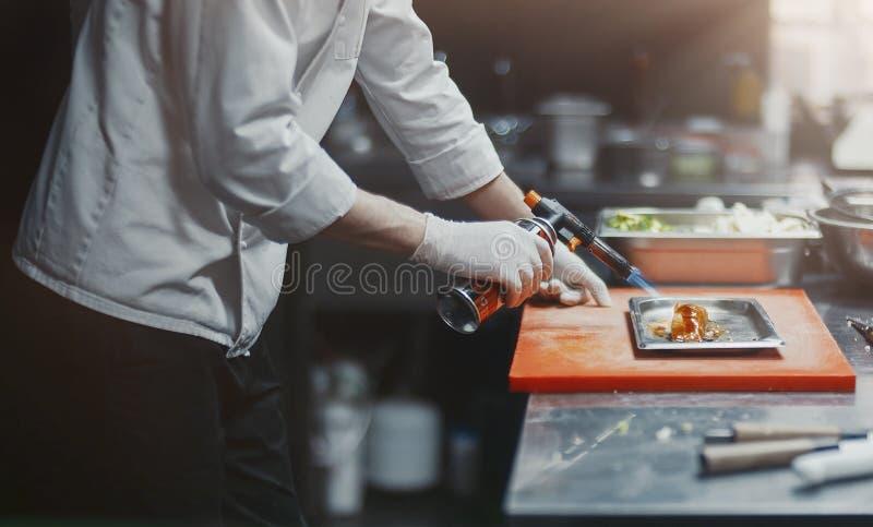 Restauracyjnego szefa kuchni kucharza narządzania fileta łososiowy flambe w otwartej kuchni obrazy royalty free