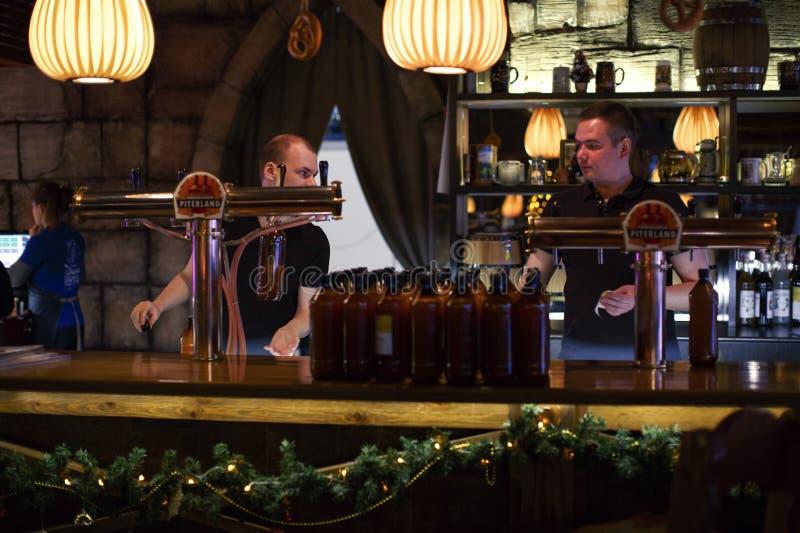 Restauracyjni barmany nalewają warzącego piwo w plastikowe butelki obrazy stock