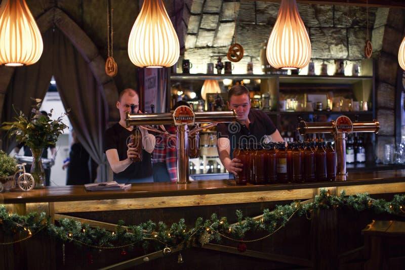 Restauracyjni barmany nalewają warzącego piwo w plastikowe butelki fotografia stock