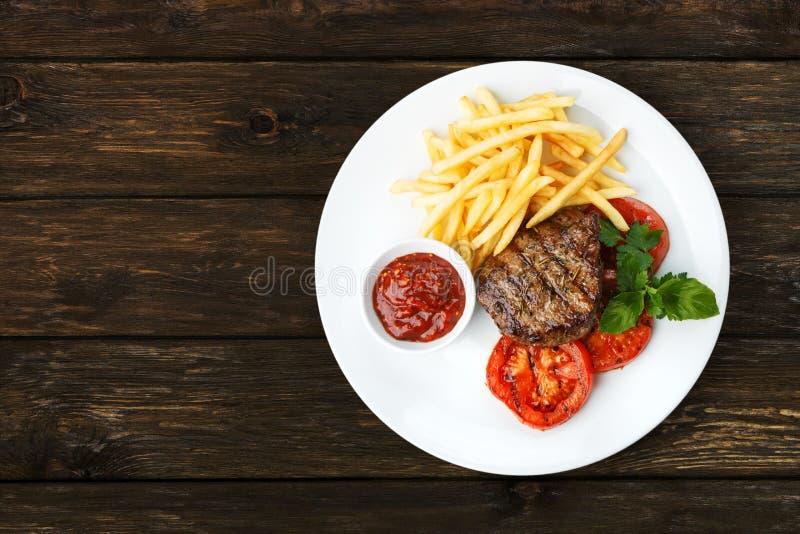 Restauracyjny jedzenie - wzmacnia piec na grillu stek z francuskimi dłoniakami fotografia stock