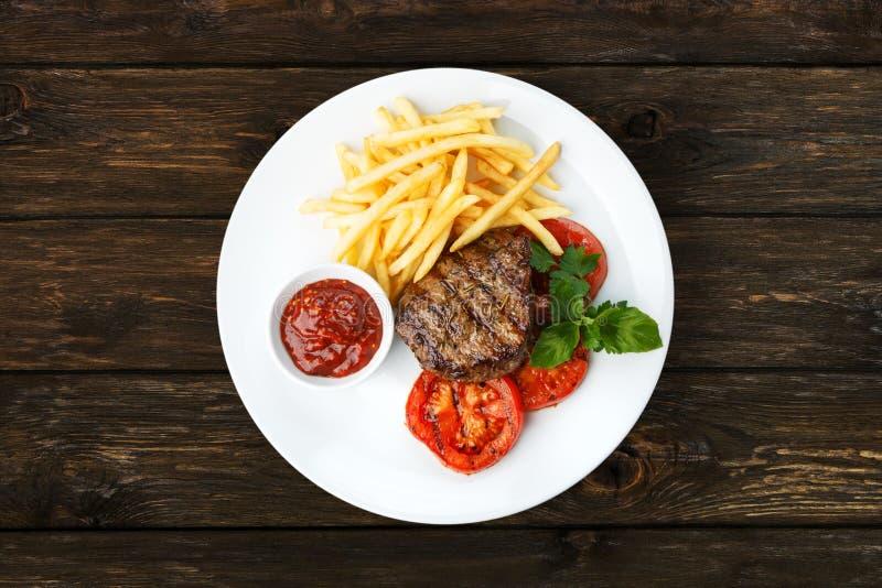 Restauracyjny jedzenie - wzmacnia piec na grillu stek z francuskimi dłoniakami obraz royalty free