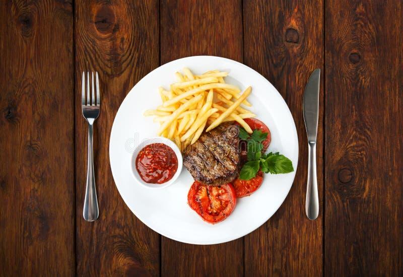 Restauracyjny jedzenie - wzmacnia piec na grillu stek z francuskimi dłoniakami obrazy royalty free