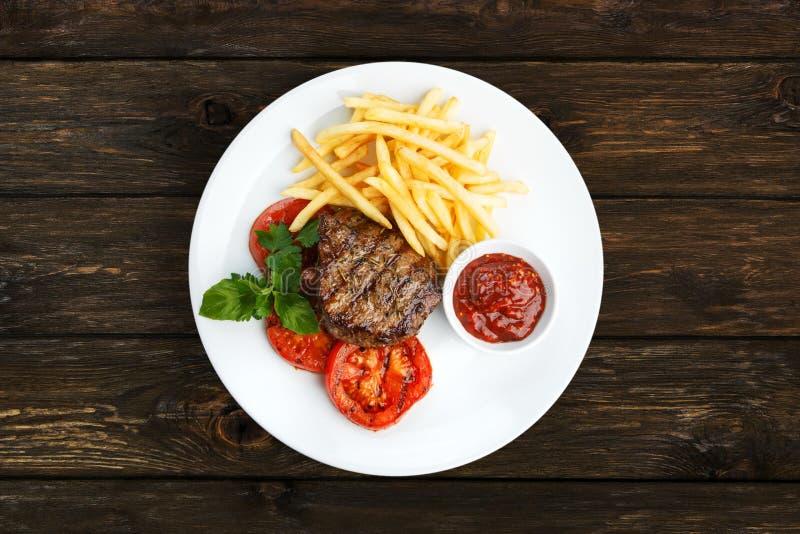 Restauracyjny jedzenie - wzmacnia piec na grillu stek z francuskimi dłoniakami zdjęcie stock